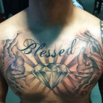"""tatoeage van een grote diamand met daarboven """"blessed"""" en er omheen lichtstralen en twee handen die uit wolken lijken te komen"""