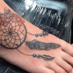 Mooie dromenvanger tatoeage met veren eraan op de voet van een vrouw