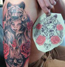 tattoo van een meisje met een tijgervel omringt met rozen, geplaatst op bovenarm