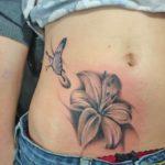 Vrolijke tattoo op de onderbuik met een lelie en een paarse vlinder