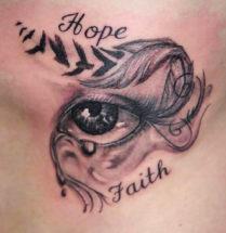 Oog tatoeage op de zij met de tekst Hope en Faith