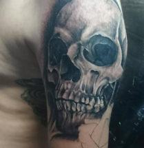 Realistische skull tatoeage geplaatst op de bovenarm door tattooshop Dutchink