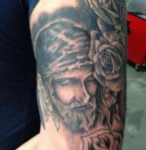 tatoeage van Jezus met dornen kroon en rozen geplaatst op de bovenarm