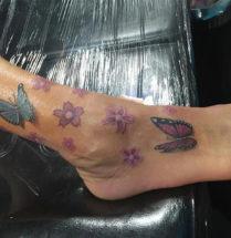 tatoeage van kleine paarse bloemetjes en twee vlinder op de voet