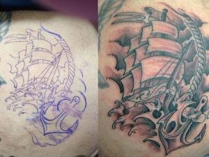 Zwart witte old school tatoeage van een schip en een anker op een woeste zee geplaatst op de borst