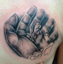 tattoo van een klein baby handje in een grotere hand met de initialen MJ eronder