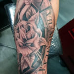 Romeinse tekens bijgevoegd en een roos verwerkt in een tatoeage