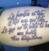 spaanse tekst tattoo over familie op de bicep