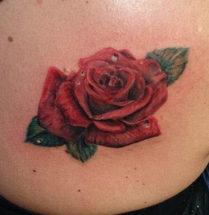 Tatoeage van een rode roos met enkele druppels water erop