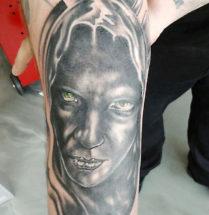 Portret tatoeage van een zwart gezicht met groene ogen die je aankijken