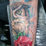 gekleurde uil tatoeage met een roos en veel details