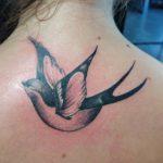 Zwart witte zwaluw tattoo in de nek