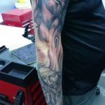 Black and grey tattoo sleeve van jezus en een biddende vrouw