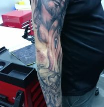 Black and grey tattoo sleeve van jezus en een biddende vrouw