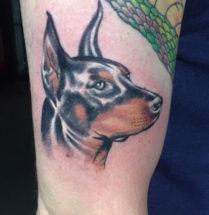 Tattoo van hond met glimmend gezicht.