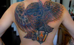 Creatieve uilen tattoo met veel kleur geplaatst over de gehele rug