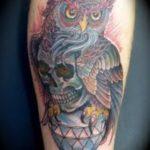 Uilen tatoeage gecombineerd met een skull tattoo geplaatst op de bovenarm