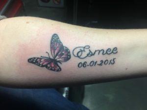 Vlinder en namen tattoo op onderarm