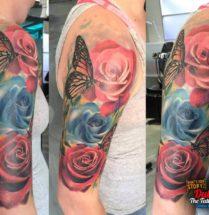 Bloemen en vlinder op bovenarm