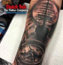 Boot en kompas op onderarm