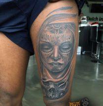 Chicano gezicht en schedel op bovenbeen