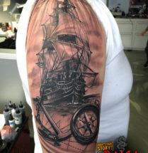 Oude boot met compas en anker op bovenarm