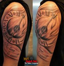 Klok met tekst tattoo op bovenarm